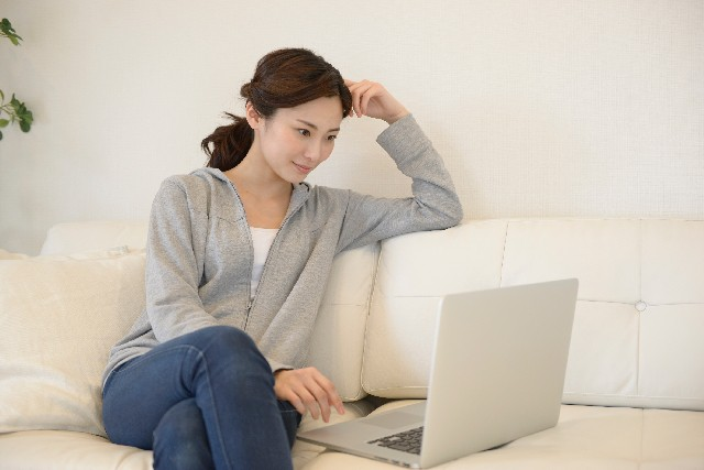 足を組んで、パソコンをする女性
